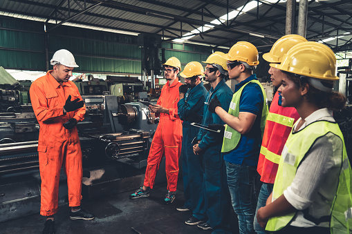 Skillful worker attending brief meeting in the factory . Industrial people and manufacturing labor concept .