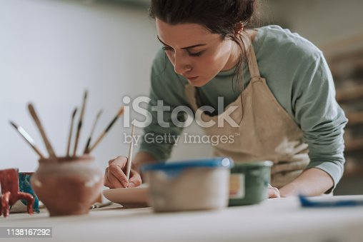 Close up portrait of beautiful brunette lady drawing on clay plate while leaning over the table with pottery and paints