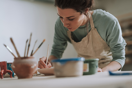 Skillful young woman in apron painting pottery at workshop