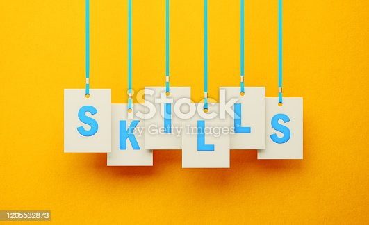 Skills on white price tag hanging from blue ribbons over yellow background. Horizontal composition. Skills concept.