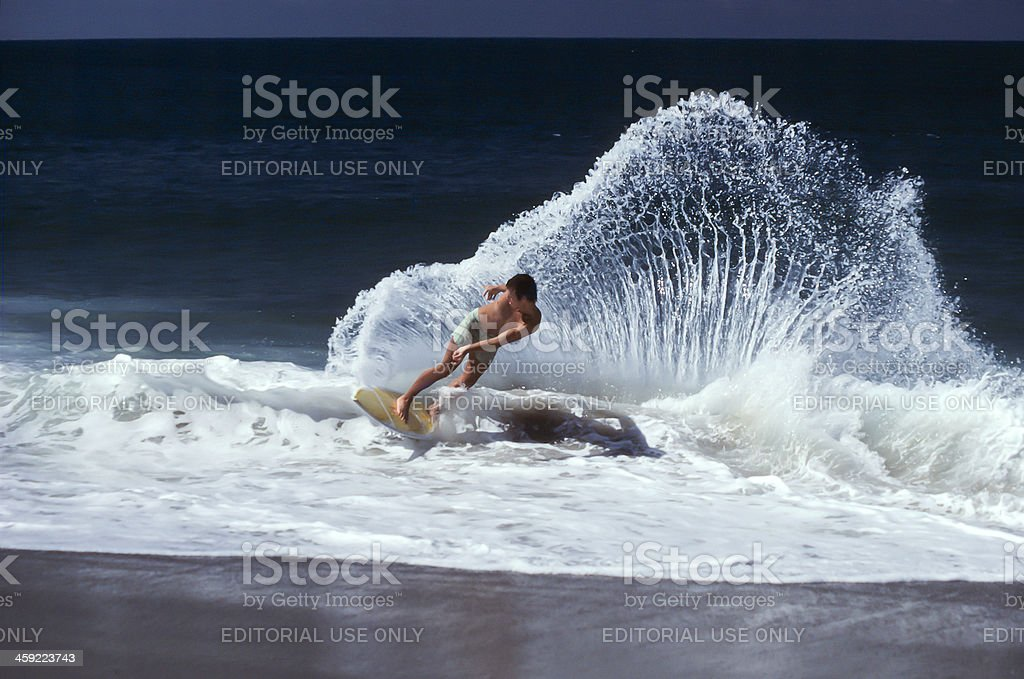Skimboarder hitting wave onshore. stock photo
