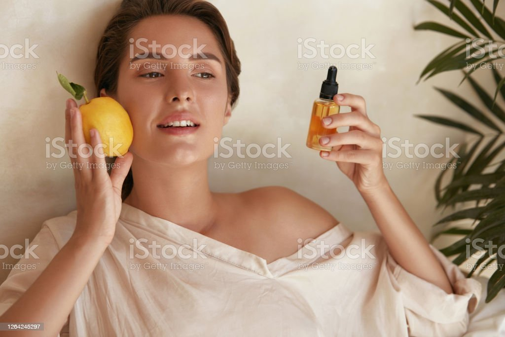 Skin Care. Beauty Portrait Of Woman Holding Lemon And Bottle Near Face. Natural Cosmetic Product For Hydrated Healthy Facial Derma. Essential Oil And Vitamin C For Anti-Aging Therapy. Skin Care. Beauty Portrait Of Woman Holding Lemon And Bottle Near Face. Natural Cosmetic Product For Hydrated Healthy Facial Derma. Essential Oil And Vitamin C For Anti-Aging Therapy. 20-29 Years Stock Photo
