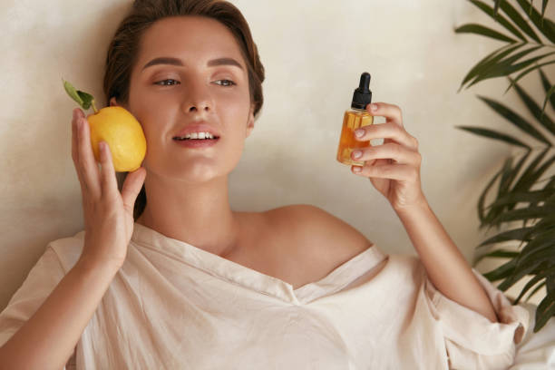 Skin Care. Beauty Portrait Of Woman Holding Lemon And Bottle Near Face. Natural Cosmetic Product For Hydrated Healthy Facial Derma. Essential Oil And Vitamin C For Anti-Aging Therapy. Skin Care. Beauty Portrait Of Woman Holding Lemon And Bottle Near Face. Natural Cosmetic Product For Hydrated Healthy Facial Derma. Essential Oil And Vitamin C For Anti-Aging Therapy. antiaging stock pictures, royalty-free photos & images