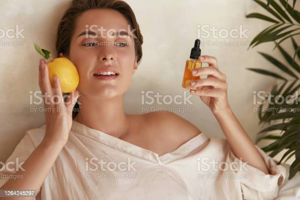 Skin Care Beauty Portrait Of Woman Holding Lemon And Bottle Near Face Natural Cosmetic Product For Hydrated Healthy Facial Derma Essential Oil And Vitamin C For Antiaging Therapy Stock Photo - Download Image Now