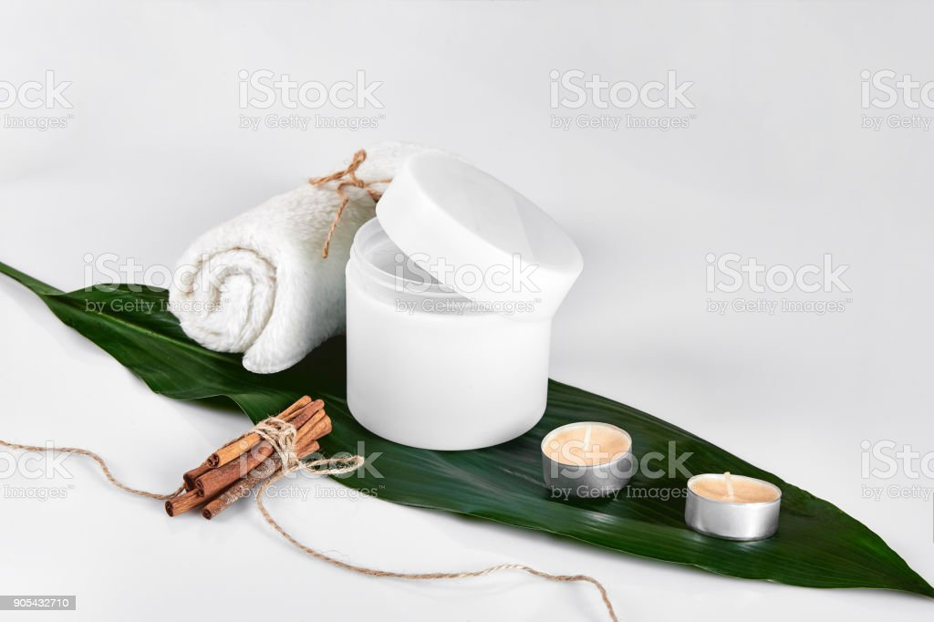 Tratamento de beleza cuidados com a pele com pote de hidratante de corpo. Loção de corpo branco com grandes folhas verdes sobre fundo claro - foto de acervo