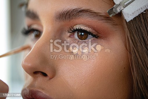 Professional model in a beauty salon enjoying getting makeup on