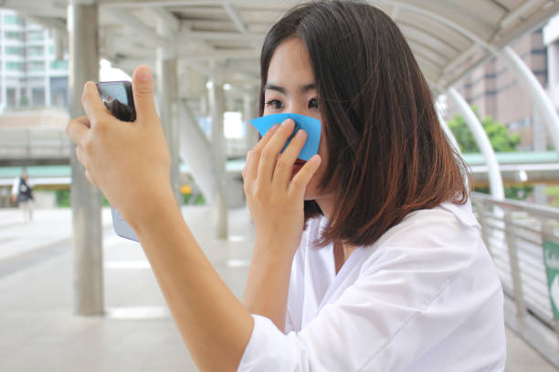 Skin care concept, Beautiful asian girl using oil remover paper on her face and looking at smartphone on street background Skin care concept, Beautiful asian girl using oil remover paper on her face and looking at smartphone on street background blotting paper stock pictures, royalty-free photos & images
