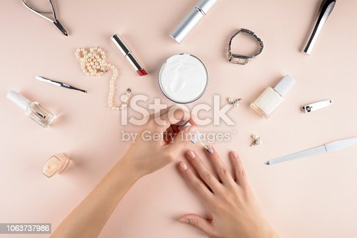 istock Skin care concept. Woman brushing nails on pink background. Flat lay. Top view 1063737986
