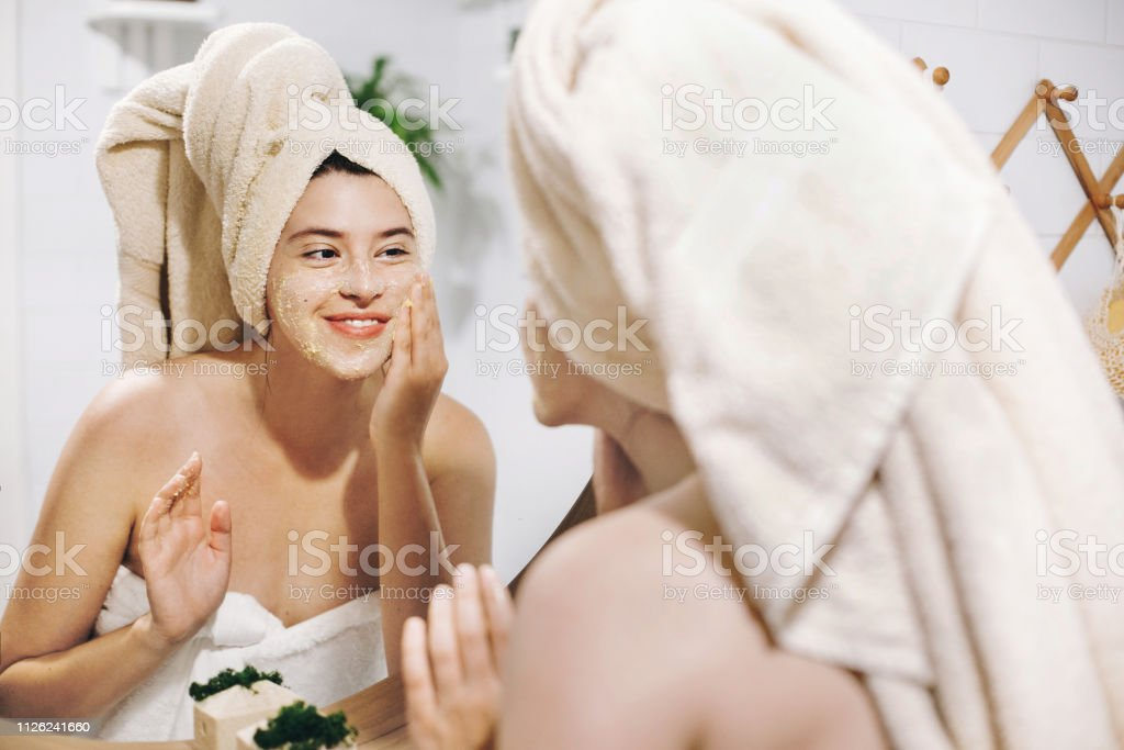 Skin Care concept. Young happy woman in towel making facial massage with organic face scrub and looking at mirror in stylish bathroom. Girl applying scrub cream, peeling and cleaning skin Skin Care concept. Young happy woman in towel making facial massage with organic face scrub and looking at mirror in stylish bathroom. Girl applying scrub cream, peeling and cleaning skin Acne Stock Photo