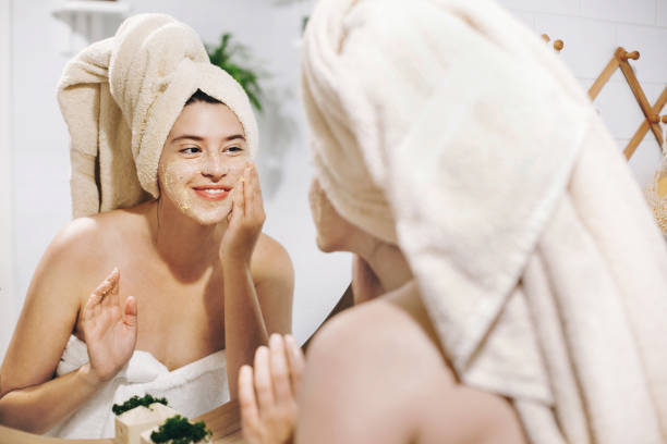 Skin Care concept. Young happy woman in towel making facial massage with organic face scrub and looking at mirror in stylish bathroom. Girl applying scrub cream, peeling and cleaning skin Skin Care concept. Young happy woman in towel making facial massage with organic face scrub and looking at mirror in stylish bathroom. Girl applying scrub cream, peeling and cleaning skin antiaging stock pictures, royalty-free photos & images