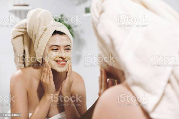 Skin Care Concept Young Happy Woman In Towel Making Facial Massage With Organic Face Scrub And Looking At Mirror In Stylish Bathroom Girl Applying Scrub Cream Peeling And Cleaning Skin Stock Photo - Download Image Now