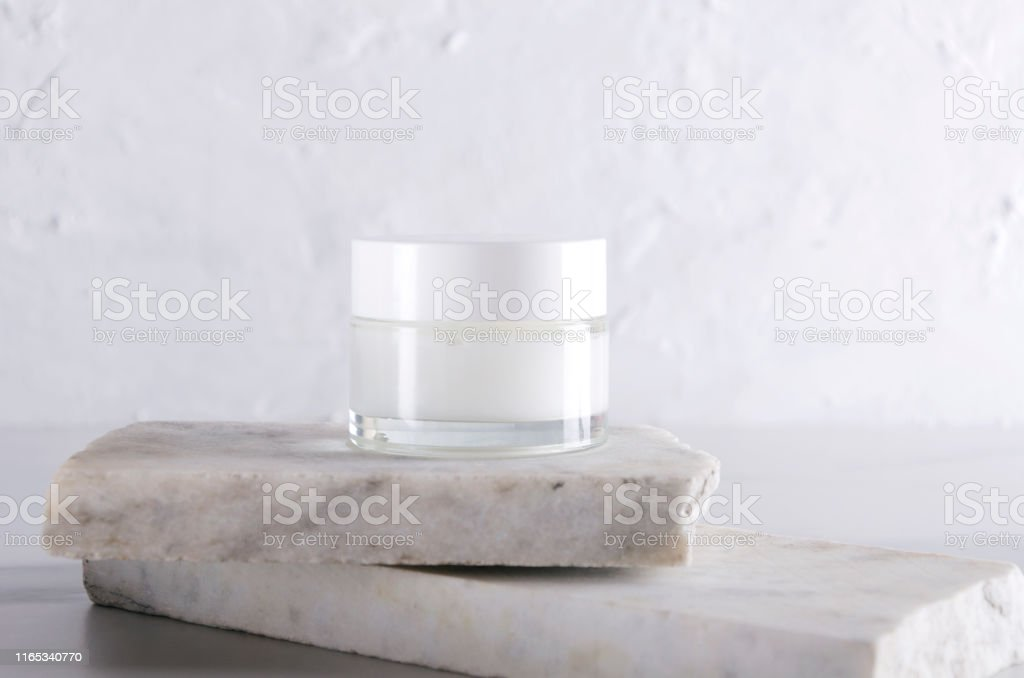 Cosmetic skincare jar on the pieces of white marble against white...