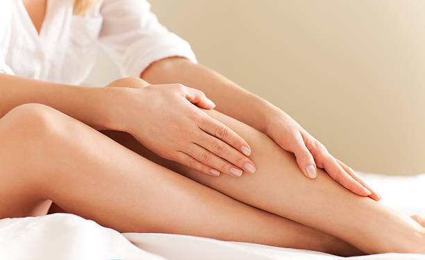 Skin Care Close up of a perfect female legs. Woman applying moisturizer.  human leg stock pictures, royalty-free photos & images