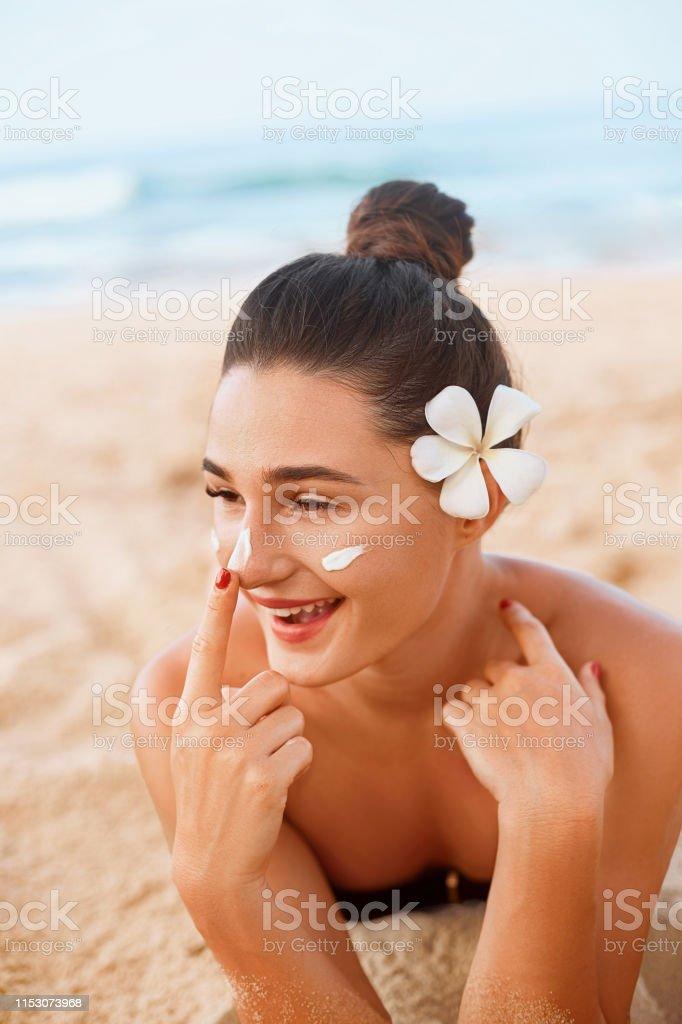 Skin care. Sun protection. Beautiful Woman In Bikini apply sun cream...