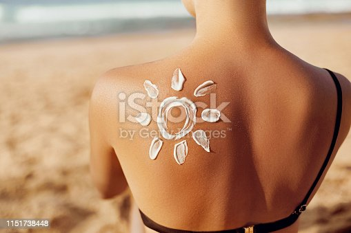 Skin care. Sun protection. Woman apply sun cream. Woman With Suntan Lotion On Beach In Form Of The Sun. Portrait Of Female With  Drawn Sun On A Shoulder. Suncream. Girl Holding Moisturizing Sunblock.