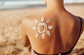 Skin care. Sun protection. Woman apply sun cream. Woman With Suntan Lotion On Beach In Form Of The Sun. Portrait Of Female With  Drawn Sun On A Shoulder. Suncream. Girl Holding Moisturizing Sunblock.