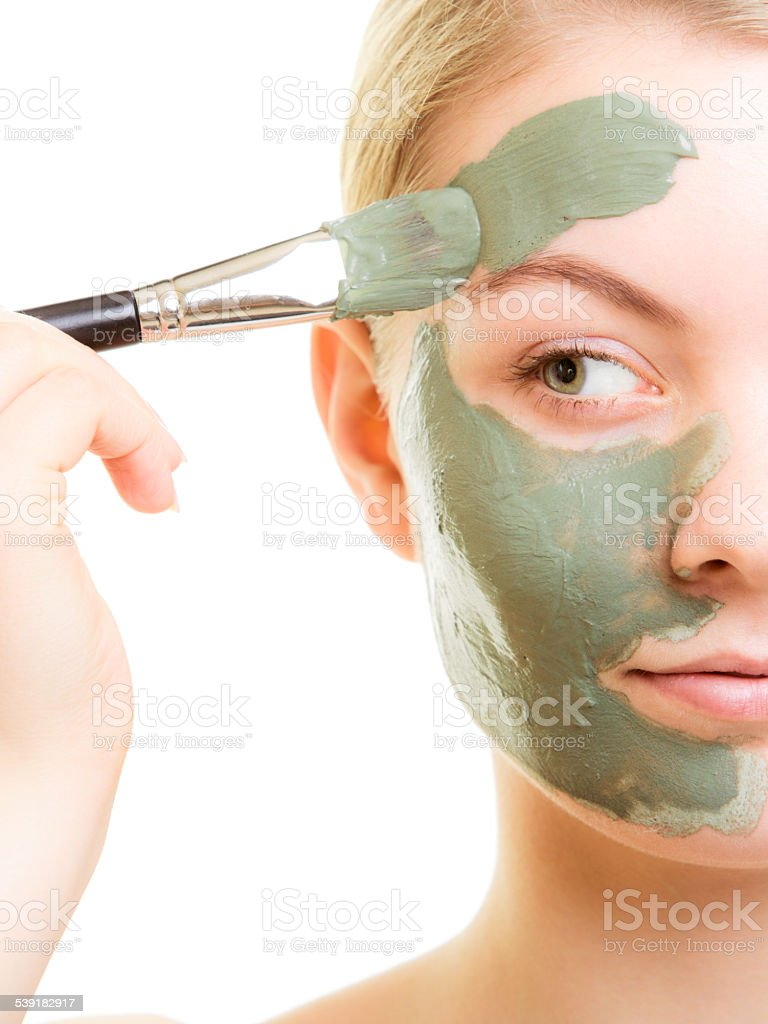 Skin care. Woman applying clay mud mask on face. stock photo