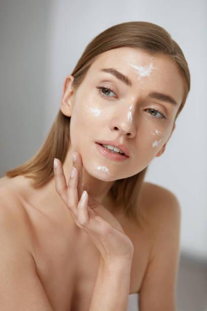 Skin care. Woman applying facial cream on beauty face closeup – zdjęcie