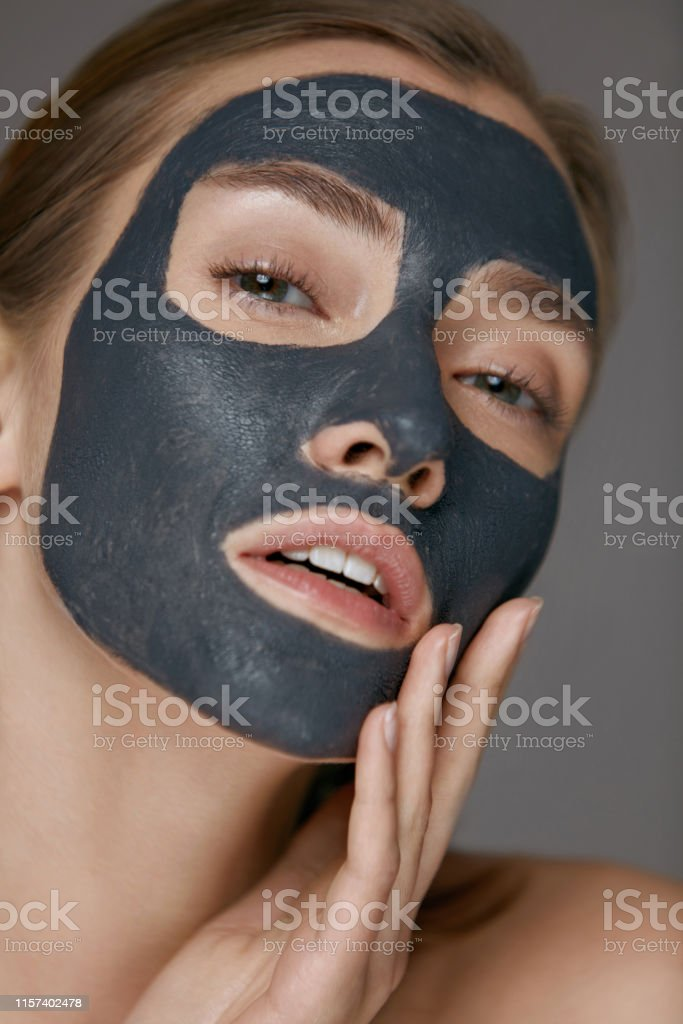 Skin care. Woman face with cosmetic spa clay mask closeup. Girl model...