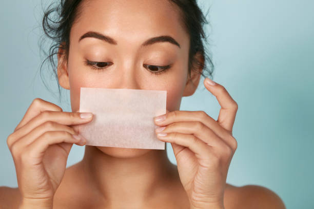 Skin care. Woman holding facial oil blotting paper portrait Skin care. Woman holding facial oil blotting paper portrait. Closeup of beautiful asian girl model with natural face makeup looking at oil absorbing tissue, beauty product. blotting paper stock pictures, royalty-free photos & images