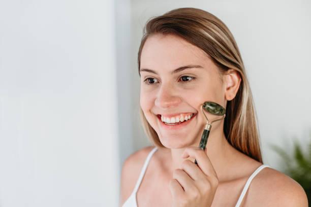 người phụ nữ chăm sóc da sử dụng con lăn mặt ngọc bích - face roller hình ảnh sẵn có, bức ảnh & hình ảnh trả phí bản quyền một lần