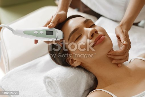 istock Skin Care. Women Analyzing Facial Skin With Analyzer. Beauty 936879772