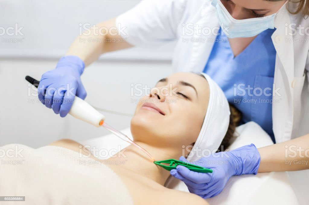 Skin care. Young woman receiving facial beauty treatment. Facial therapy. Anti-aging procedures. stock photo