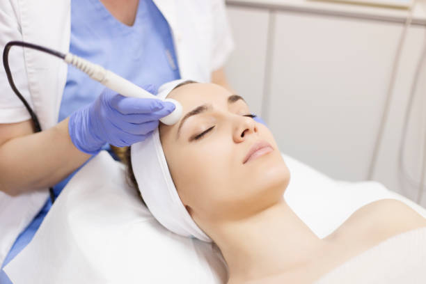 Skin care. Young woman receiving facial beauty treatment. Facial therapy. Anti-aging procedures. Skin care. Young woman receiving facial beauty treatment. Facial therapy. Anti-aging procedures. tighten stock pictures, royalty-free photos & images