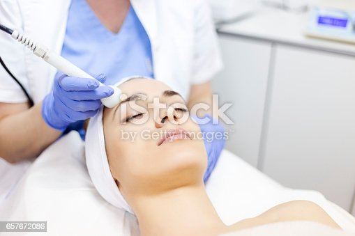 istock Skin care. Young woman receiving facial beauty treatment. Facial therapy. Anti-aging procedures. 657672086