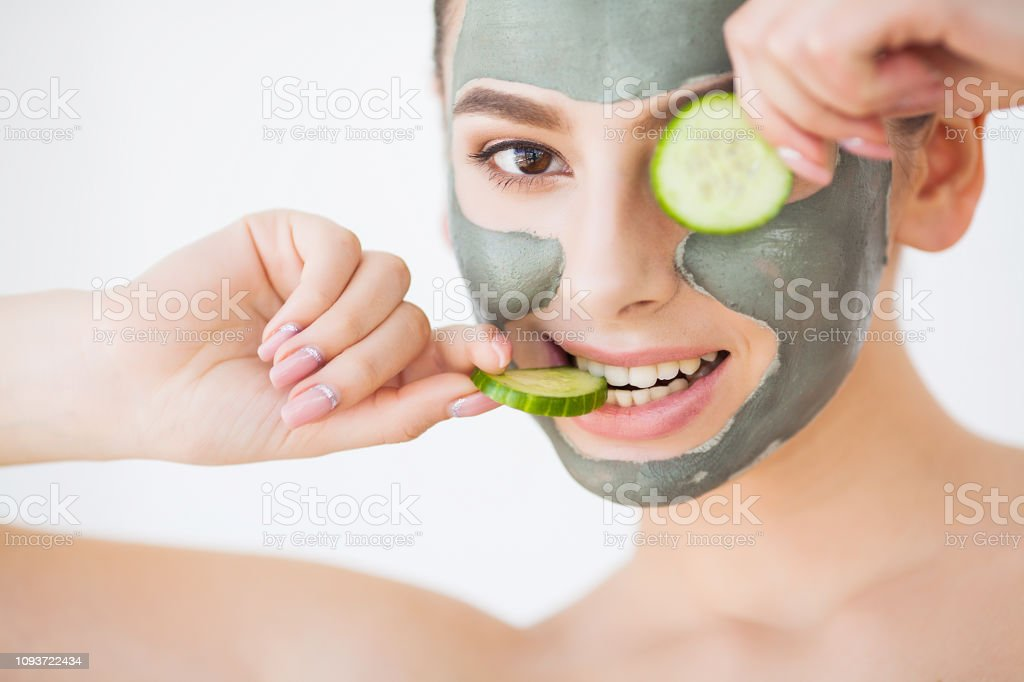 Skin Care. Young Woman With Cosmetic Clay Mask Holding Cucumber At...