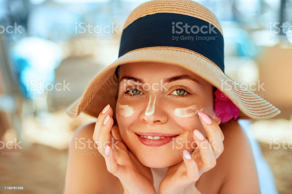 Skincare. Beauty Concept. Young pretty woman applying sun cream  and touch own face. Female in hat smear  sunscreen lotion on skin. Skin Protection and dermatology. Skincare. Beauty Concept. Young pretty woman applying sun cream  and touch own face. Female in hat smear  sunscreen lotion on skin. Skin Protection and dermatology. Adult Stock Photo