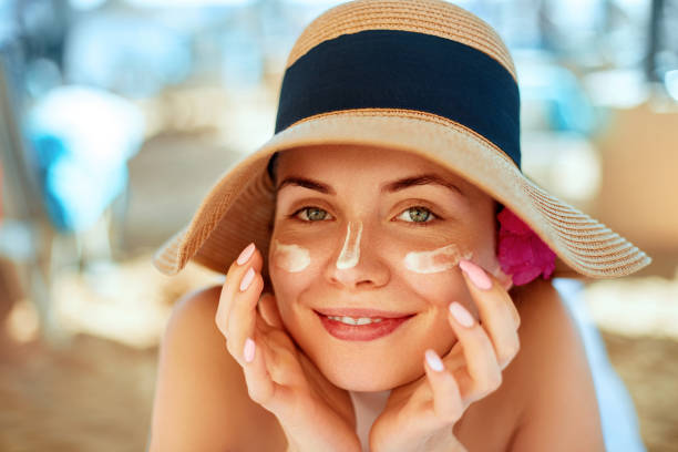 skincare. beauty concept. young pretty woman applying sun cream  and touch own face. female in hat smear  sunscreen lotion on skin. skin protection and dermatology. - abbronzarsi foto e immagini stock