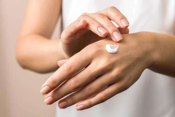 huidverzorging. close-up mening van de hand die van de vrouw hen met room hydrateert. huidverzorging - creme huid stockfoto's en -beelden