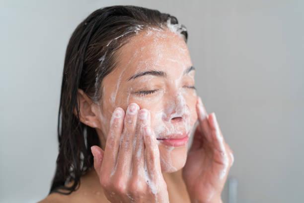 huidverzorging vrouw wassen gezicht in douche - vrouw schoonmaken stockfoto's en -beelden