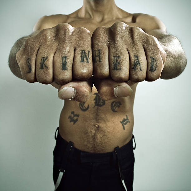 skinhead showing off knuckle tattoo - knuckle stock photos and pictures