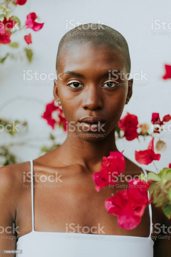 Skinhead woman surrounded by red flowers stock photo