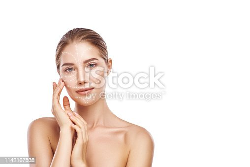 Skin-lifting treatment. Portrait of beautiful and young woman touching her perfect skin with lifting arrows on it. Isolated on white background. Skin care concept. Cosmetology. Plastic surgery