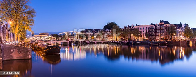Panoramic view of the Magere Brug or Skinny Bridge with reflection in the still waters of the Amstel river in Amsterdam at twilight, Holland