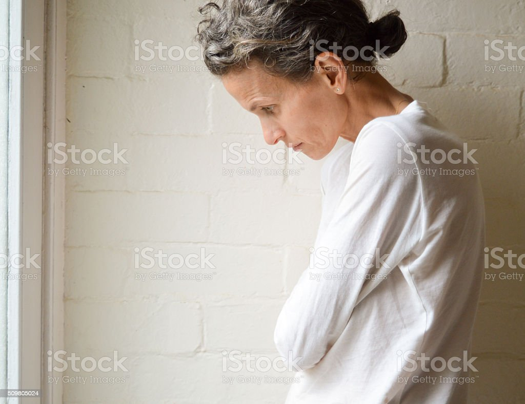 Skinny, sad mature woman stock photo