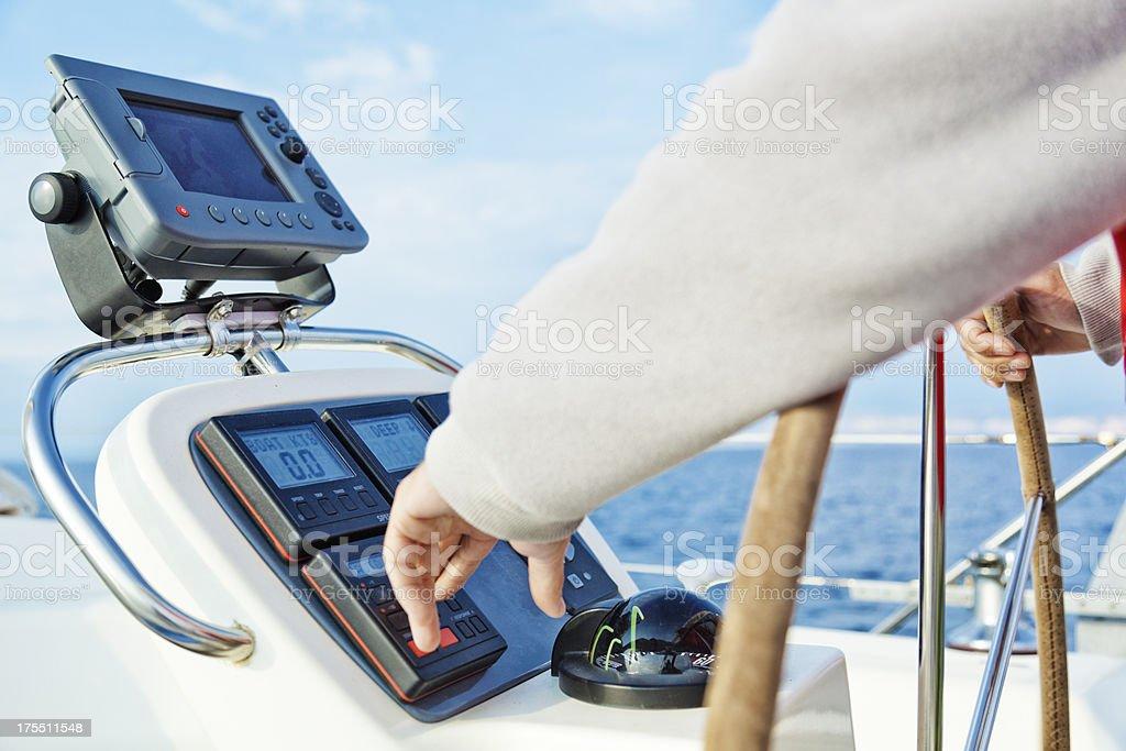 skipper adjusting yacht's auto pilot stock photo
