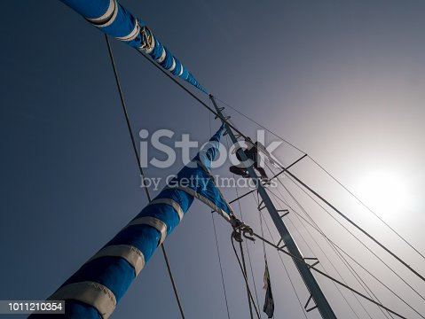 1011210354 istock photo Skipper climbs up on the pole of a sail boat. View from deck up to sky. 1011210354