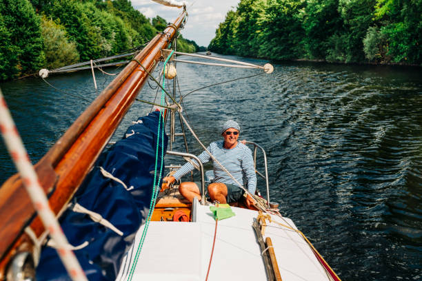 Skipper on his sailboat traveling in canal, Germany, Brandenburg-State stock photo