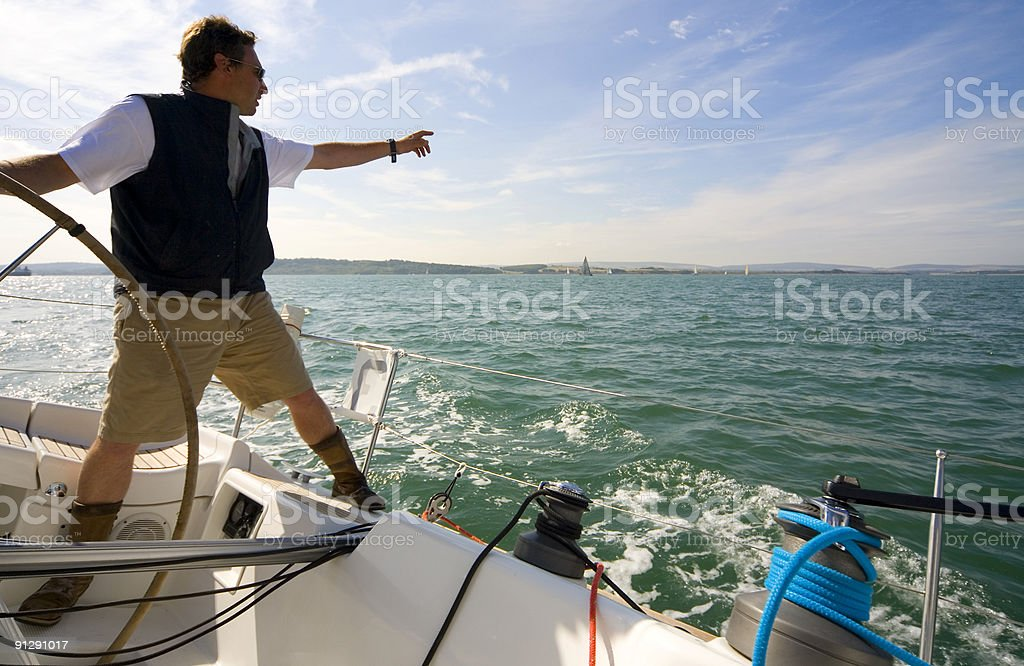 Skipper on Sailing Boat or Yacht Pointing To The Horizon royalty-free stock photo