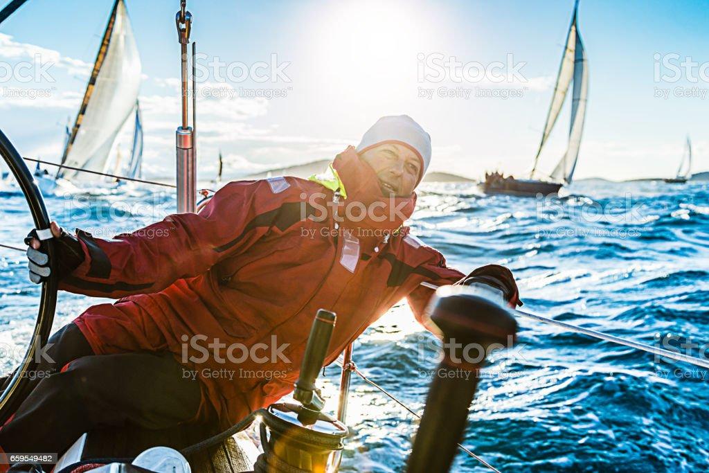 Skipper sailing on sailboat during regatta stock photo
