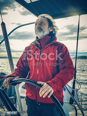 Skipper sailing on sailboat holding steering wheel on spring sunset. Taken by Apple iPhone Xs Max.