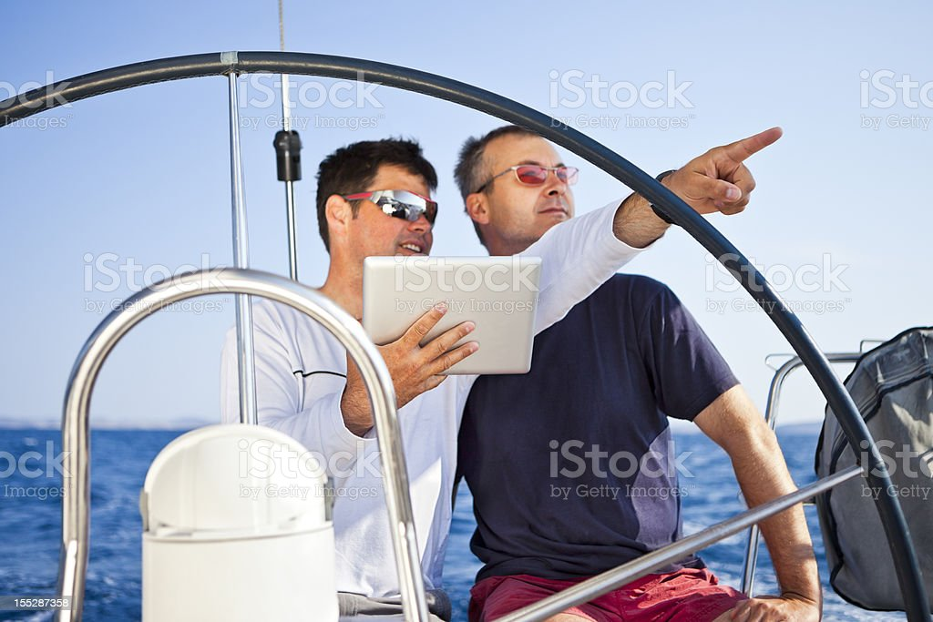 Skipper using digital tablet on sailboat - Royalty-free 30-39 Years Stock Photo