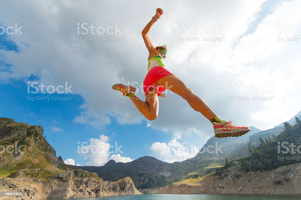 Skipping girl as he runs near a mountain lake stock photo