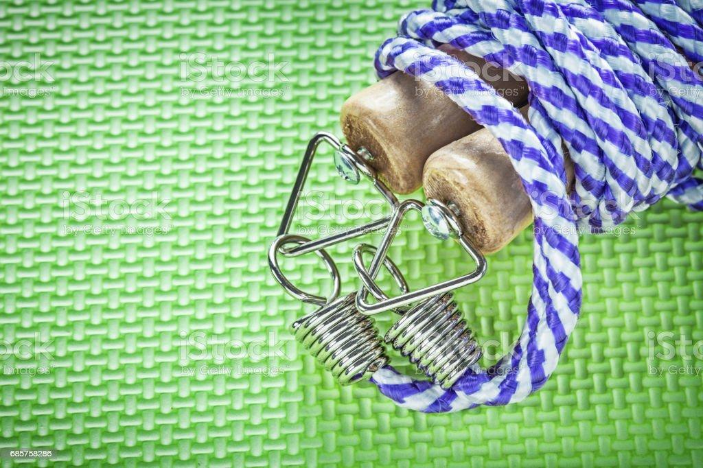 Skipping rope with wooden handles on green surface fitness conce royaltyfri bildbanksbilder