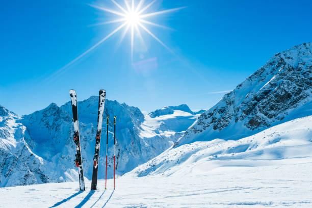 skis et bâtons de ski sur pente distant - station de ski photos et images de collection