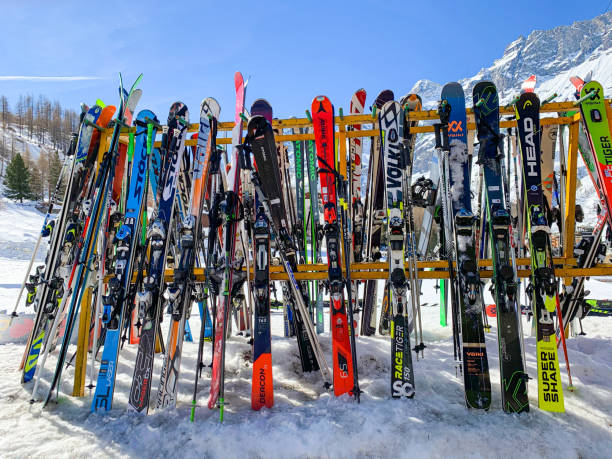 Skis and ski poles put in rack at slope stock photo